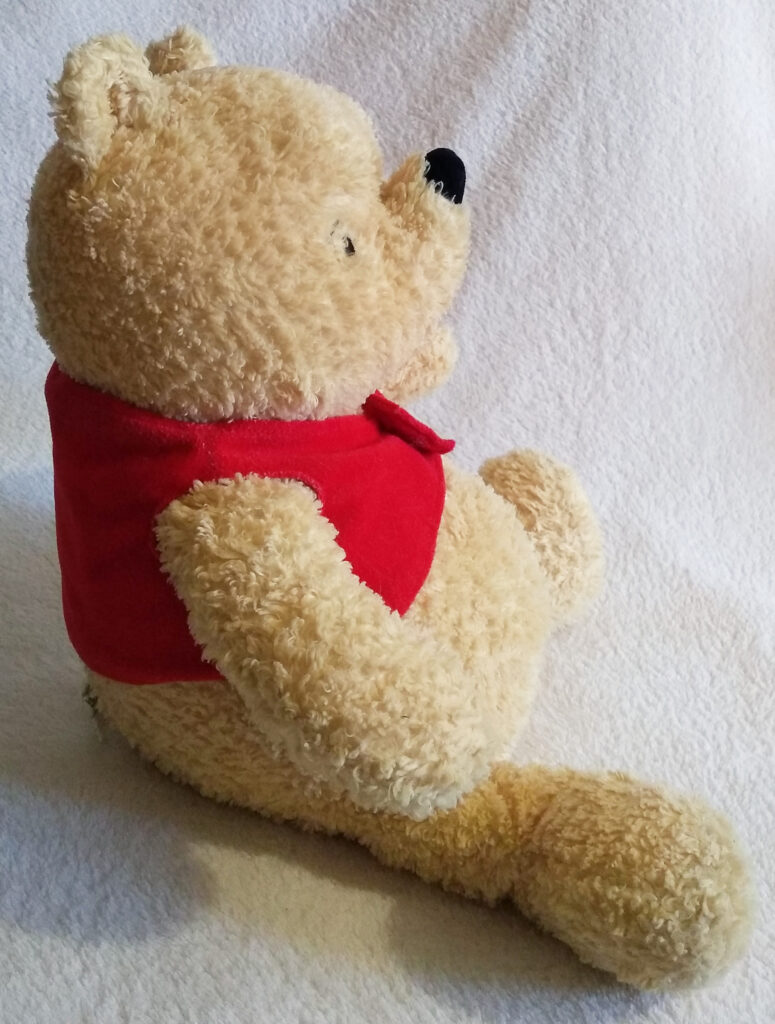 A side view of Winnie the Pooh, Classic Pooh plush by Golden Bear